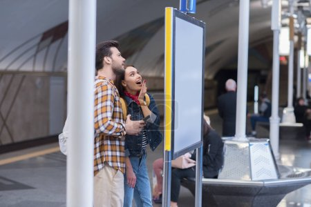 side view of surprised female tourist with boyfriend looking at information board at subway station