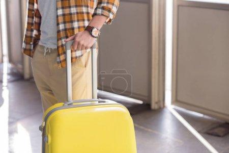Foto de Recortada de turista masculino elegante tiro con reloj de pulsera y bolso con ruedas - Imagen libre de derechos