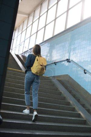 Photo pour Vue arrière du touriste femelle avec sac à dos va à l'étage dans le métro - image libre de droit