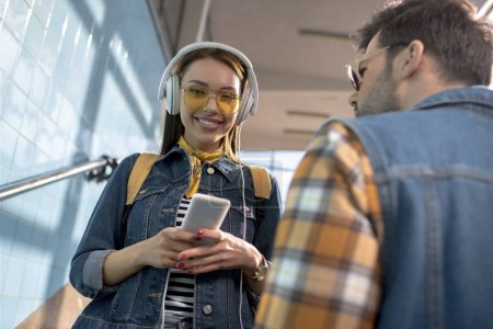 smiling stylish female tourist in sunglasses with headphones holding smartphone and boyfriend standing near at subway