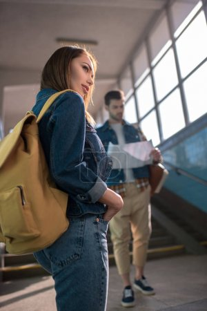 Photo for Young female traveler with backpack and boyfriend looking at map behind - Royalty Free Image