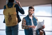 stylish male traveler with map in hand asking for help woman with headphones and backpack at subway