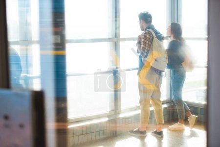 Photo pour Couple de voyageurs élégants avec sacs à dos dans le métro - image libre de droit