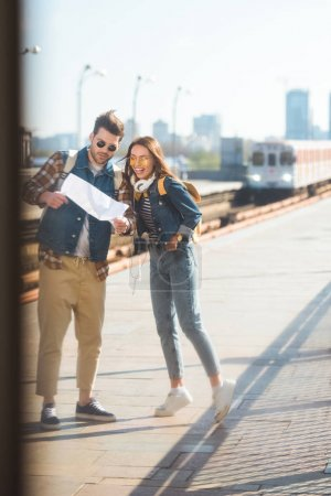 stylish couple of travelers with backpacks in sunglasses looking at map at outdoor subway station