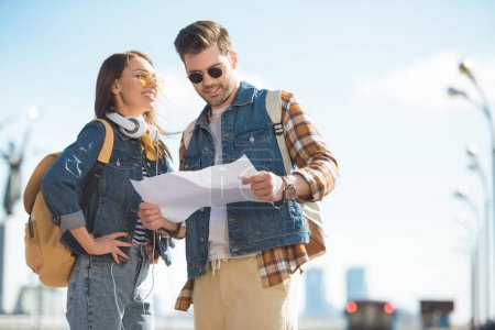 Photo for Young stylish couple of travelers with backpacks in sunglasses looking at map - Royalty Free Image
