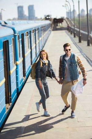 Photo for High angle view of stylish tourists in sunglasses with backpacks and map at outdoor subway station - Royalty Free Image