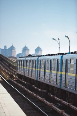 front view of train at outdoor subway station with buildings on background
