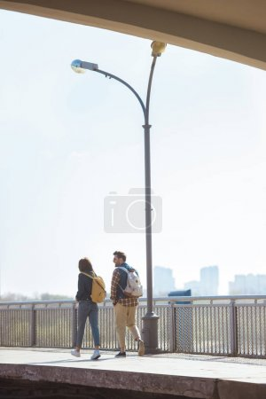 rear view of couple of tourists going at outdoor subway station