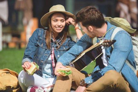 Photo pour Voyageurs élégants chapeaux avec sacs à dos et de la guitare maintenant sandwichs - image libre de droit