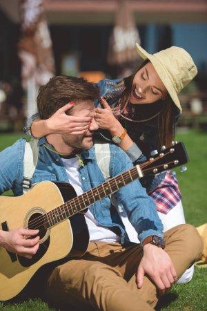 Photo pour Souriant femelle voyageur en chapeau couvrant les yeux de copain avec la guitare de derrière - image libre de droit