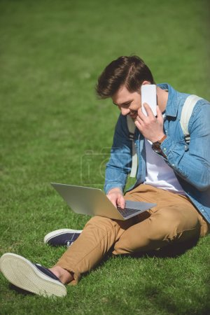 stylish man talking on smartphone and using laptop on grass