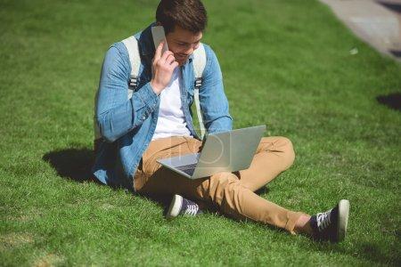 Photo pour Homme élégant parler sur smartphone et en utilisant le portable sur l'herbe - image libre de droit