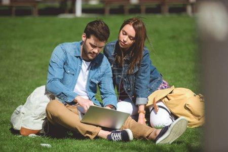 Photo pour Jeunes touristes avec sacs à dos et l'ordinateur portable assis sur l'herbe - image libre de droit