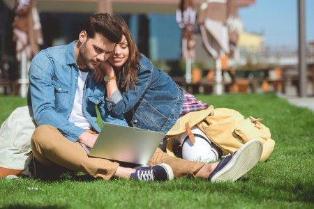 Photo pour Jeune couple élégant de voyageurs avec sacs à dos à l'aide de portable sur l'herbe - image libre de droit
