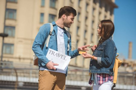 male tourist with travel newspaper giving dollar banknote to girlfriend with credit card in hand