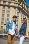 female tourist giving credit card to boyfriend with travel newspaper in hand