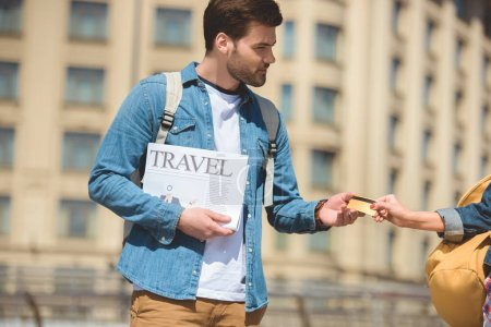 cropped image of female tourist giving credit card to boyfriend with travel newspaper in hand