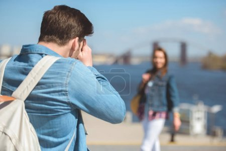 Photo for Rear view of male traveler with backpack shooting girlfriend on camera - Royalty Free Image