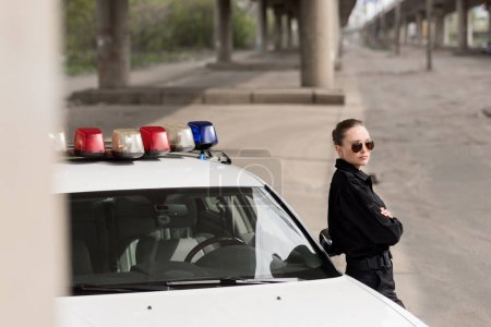Photo for Female police officer with crossed arms leaning on patrol car - Royalty Free Image