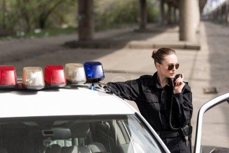 policewoman talking by radio set near patrol car