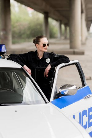 attractive female police officer standing near patrol car