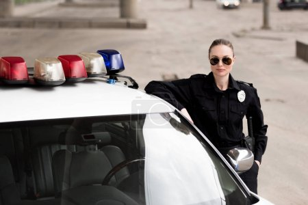 female police officer leaning on patrol car