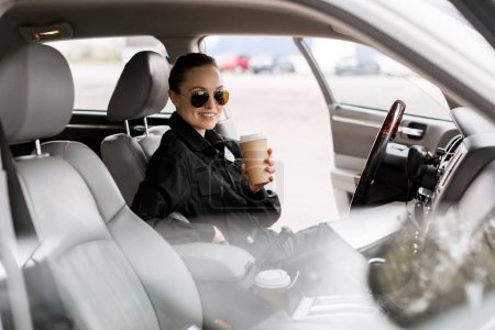 smiling policewoman with paper cup of coffee sitting in car and looking at camera