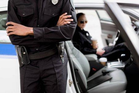 Photo pour Recadrée tir du policier avec bras croisés debout devant la voiture de police - image libre de droit