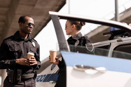 young relaxing police officers drinking coffee near police car
