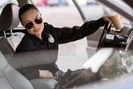attractive policewoman with paper cup of coffee sitting in car and looking at camera