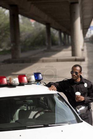 police officer with coffee to go leaning on police car on street