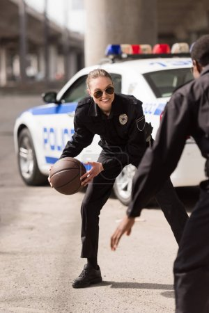active young police officers playing basketball on street