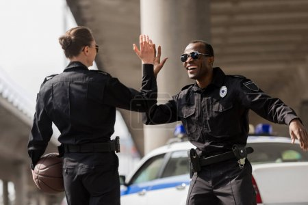 police officers with basketball ball giving high five