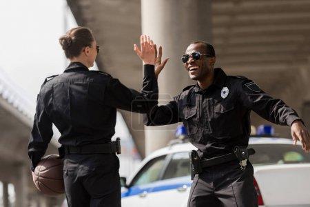 Photo pour Agents de police avec ballon de basket donnant cinq haut - image libre de droit