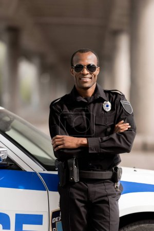 smiling african american police officer with crossed arms leaning back on car and looking at camera