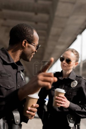 policeman pointing somewhere while drinking coffee to go with partner