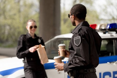 young police officers with coffee to go and paper bag with lunch having break next ot car