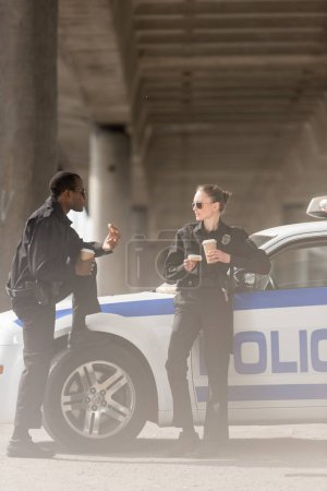police officers with coffee and doughnuts standing next to car under bridge
