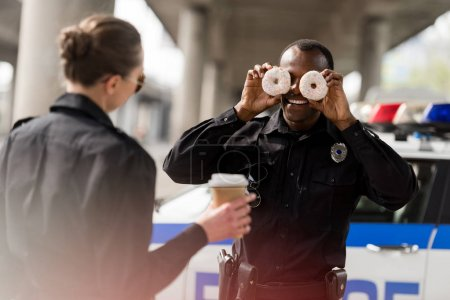 african american police officer pretending doughnuts as his eyes to amuse his partner