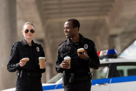 smiling police officers having coffee break with doughnuts