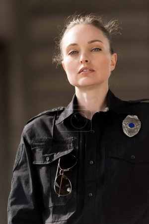 attractive female police officer in uniform looking at camera