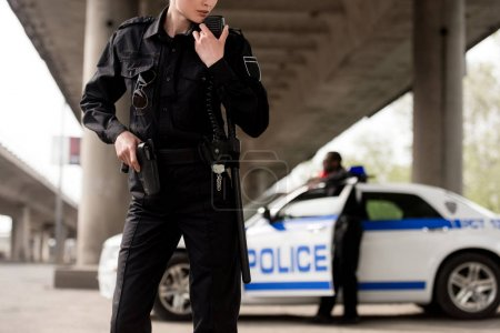cropped shot of policewoman using walkie-talkie with blurred partner near car on background