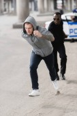 young hooded thief running from african american policeman