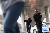 multiethnic young police officers running for thief