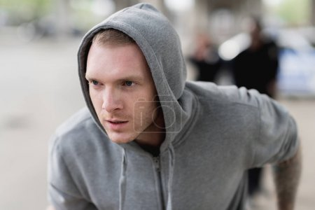 close-up shot of young hooded thief running from police