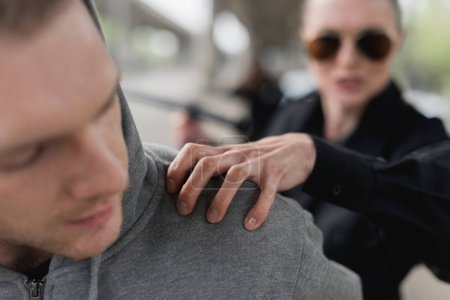 close-up shot of policewoman catching shoulder of thief