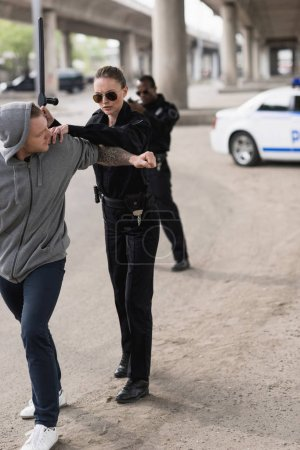 policewoman with truncheon arresting bandit and policeman standing behind and aiming by handgun