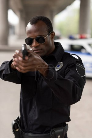 young african american policeman in sunglasses aiming by handgun