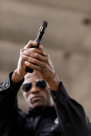 low angle view of african american policeman in sunglasses aiming by handgun