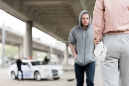 cropped shot of woman with handbag and thief in hoodie